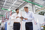 Two businessmen with tablet in factory shop floor discussing - DIGF02076