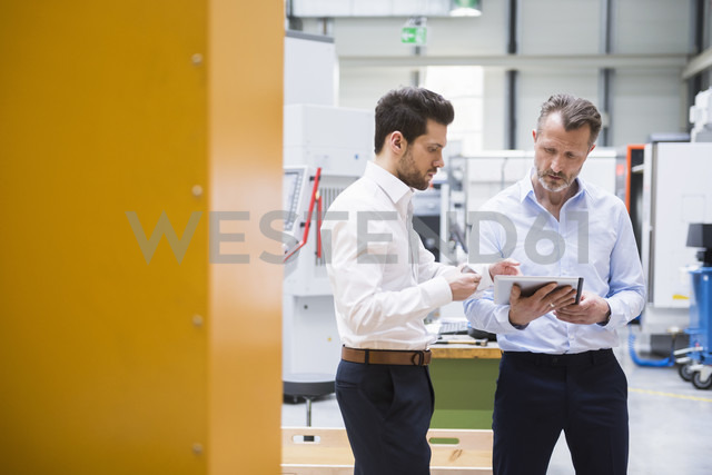 Two men with tablet and product in factory shop floor - DIGF02079 - Daniel Ingold/Westend61