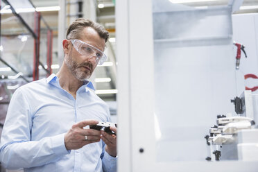 Man wearing safety goggles in factory holding product - DIGF02082