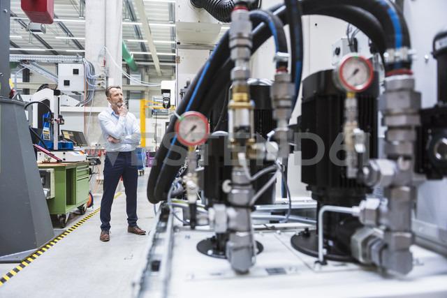 Man in factory shop floor looking at machine - DIGF02085