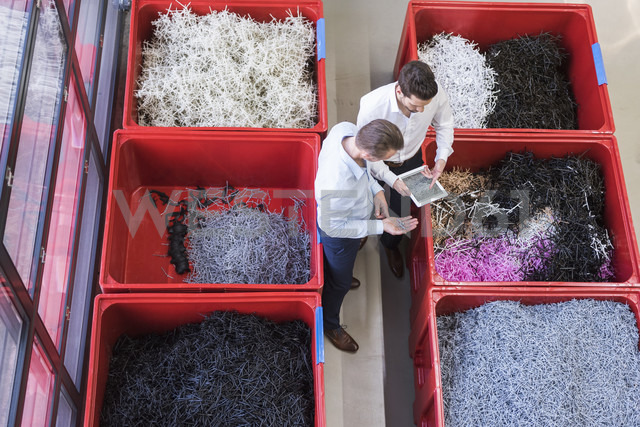 Two businessmen with tablet in factory standing at containers with shred - DIGF02088 - Daniel Ingold/Westend61