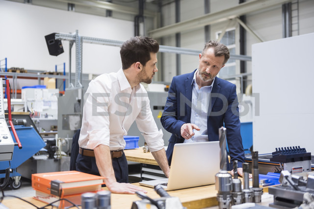 Two men at table in factory shop floor with laptop - DIGF02100 - Daniel Ingold/Westend61