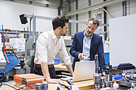 Two men at table in factory shop floor with laptop - DIGF02100