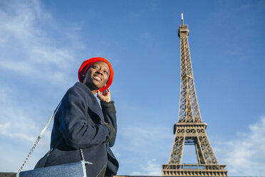 France, Paris, young woman wearing red beret in front of Eiffel Tower - KIJF01383