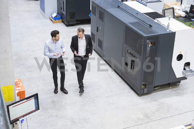 Two businessman observing industrial robots in factory - DIGF02103 - Daniel Ingold/Westend61