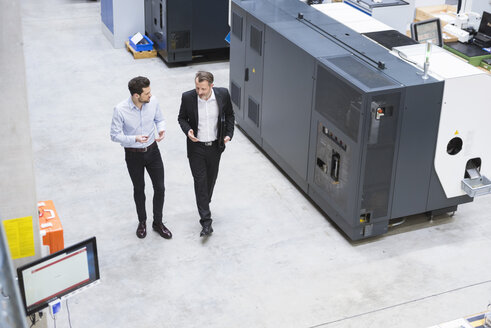 Two businessman observing industrial robots in factory - DIGF02103