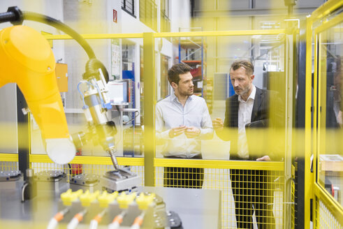 Two businessman observing industrial robots in factory - DIGF02106