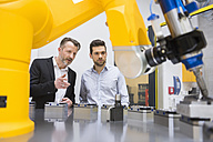 Two businessman observing industrial robots in factory - DIGF02109