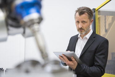 Mature businessman controlling industrial robots with digital tablet - DIGF02112