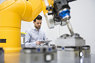 Young businessman checking automated production in factory - DIGF02115