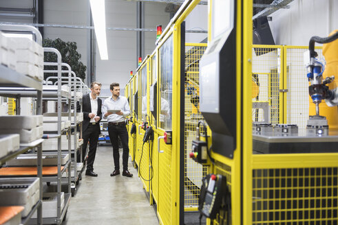 Two businessman observing industrial robots in factory - DIGF02121