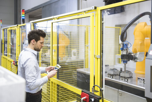 Young businessman checking automated production in factory - DIGF02124