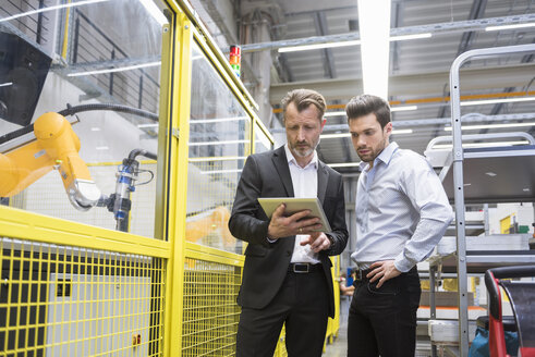 Two businessman observing industrial robots in factory - DIGF02130