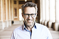 Portrait of smiling businessman with stubble wearing glasses - FMKF03965