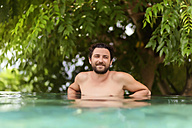 Man relaxing in swimming pool - KNTF00835