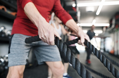 Senior in gym working out with battle ropes - HAPF01518