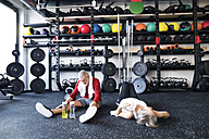 Exhausted senior couple recovering on the floor after working out in gym - HAPF01527