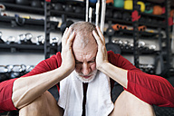 Exhausted senior man sitting on the floor after working out in gym - HAPF01530