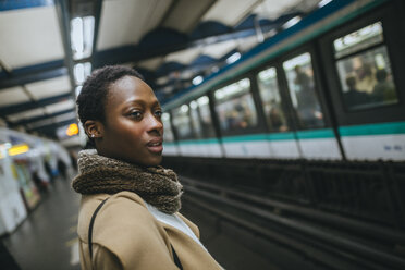 France, Paris, portrait of young woman waiting at subway station platform - KIJF01404