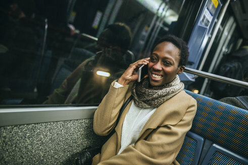 Portrait of smiling young woman on the phone in underground train - KIJF01407