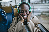 Happy young woman listening music in a bus - KIJF01413