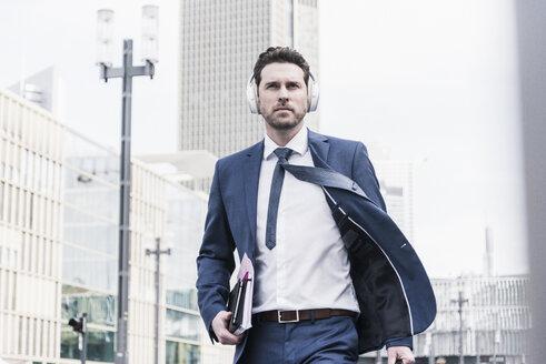 Businessman walking in the city, wearing headphones - UUF10375