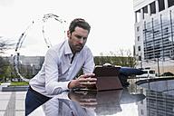 Businessman using digital tablet outdoors - UUF10384