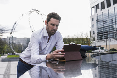 Businessman using digital tablet outdoors - UUF10384