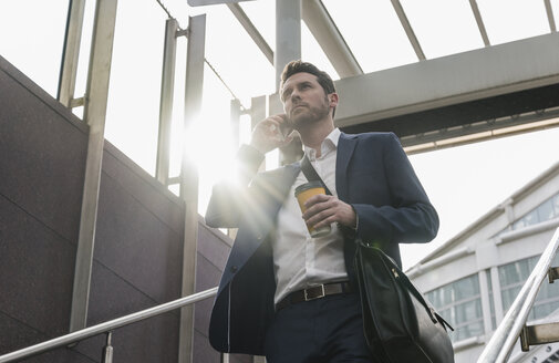 Businessman talking on the phone walking downstairs - UUF10390
