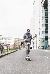Businessman skateboarding while using smartphone and earphones - UUF10393