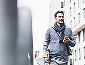 Businessman carrying skateboard, using smartphone and earphones - UUF10396