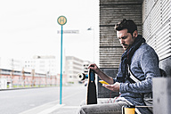 Businessman with skateboard sitting at bus stop using smartphone - UUF10399