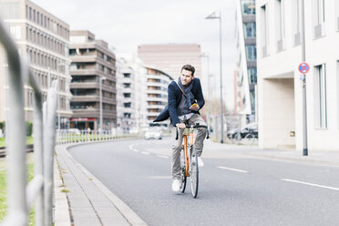 Businessman riding bicycle in the city, while using smartphone and earphones - UUF10402