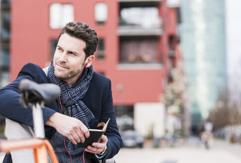 Businessman in the city with bicycle using smartphone and earphones - UUF10405