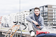 Businessman in the city with bicycle using smartphone and earphones - UUF10408
