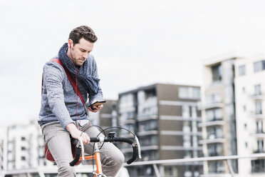 Businessman riding bicycle in the city, while using smartphone and earphones - UUF10411
