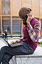 Man sitting on bench using headphones while looking at laptop - MAUF01046