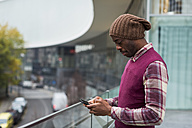Man standing on terrace using cell phone - MAUF01049