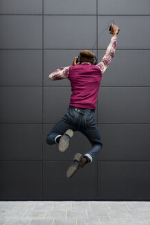Back view of happy man jumping in the air while listening music with headphones and cell phone - MAUF01064
