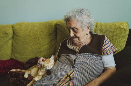 Senior woman sitting on couch stroking tabby cat - RAEF01860