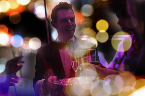 Waiter with tray serving champagne glasses on a party - ZEF13566