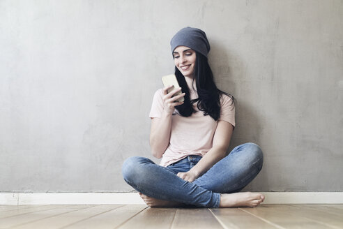 Smiling young woman sitting on the floor using cell phone - FMKF03991