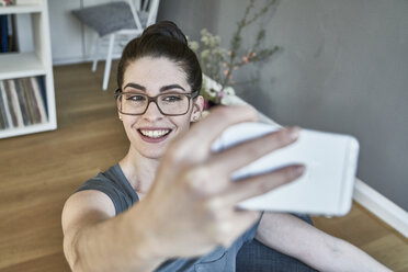 Smiling young woman taking a selfie at home - FMKF04012