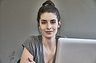 Portrait of smiling young woman with laptop - FMKF04018