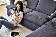 Young woman relaxing at home in living room - FMKF04036