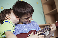 Boy playing ukulele while his little brother embracing him - ZOCF00206