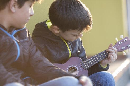 Boy playing ukulele while his friend watching him - ZOCF00218