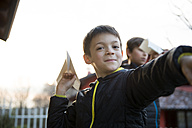 Portrait of smiling boy with paper plane - ZOCF00221
