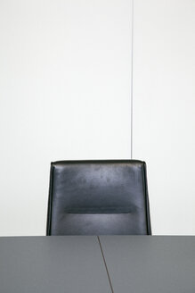 Leather chair behind table top in an office - JMF00394