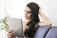 Young woman on couch using tablet - FMKF04040